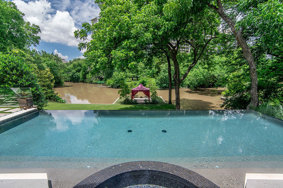The infinity-edge pool overlooks Turtle Creek, and the property's tented-gazebo.