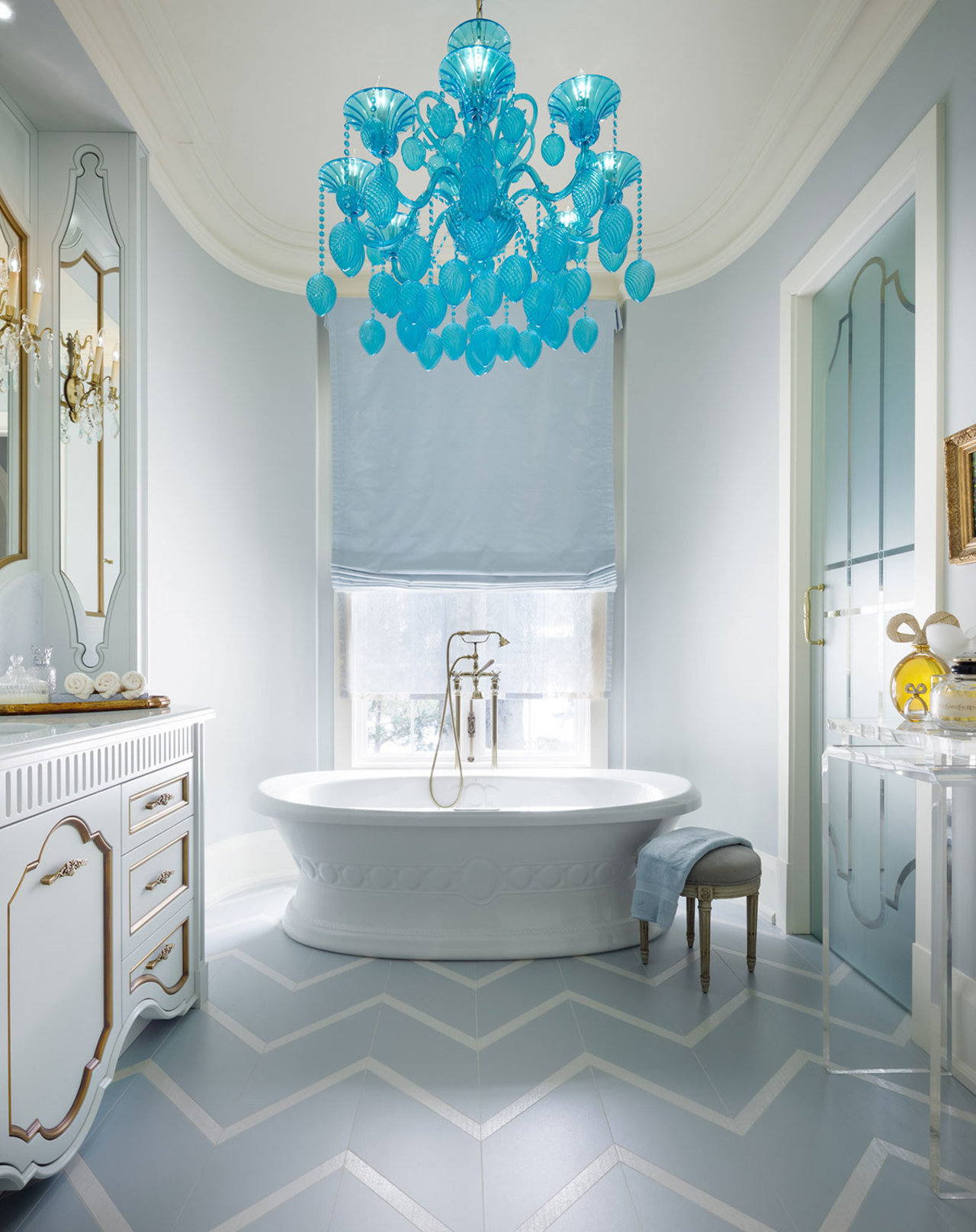 A standout blue glass chandelier over a floating tub, chevron-patterned flooring, and gold-trimmed ca